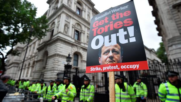 An anti-government protest placard is seen outside Downing Street during a march to protest against the British government's spending cuts and austerity measures in London on June 20, 2015. The national demonstration against austerity was organised by People's Assembly against government spending cuts.   AFP PHOTO / BEN STANSALLBEN STANSALL/AFP/Getty Images