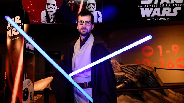 """A Stars Wars fan holds """"light sabres"""" as he poses for a photograph as he waits for a screening of """"Star Wars: The Force Awakens"""", at the Kinepolis cinema in Liege, on December 16, 2015.  AFP PHOTO / JOHN THYS / AFP / JOHN THYSJOHN THYS/AFP/Getty Images"""