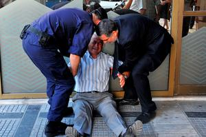(FILES)-A July 3, 2015 shows Giorgos Chatzifotiadis, assisted by an employee and a policeman, as he sits on the ground outside a national bank branch, as pensioners (unseen) queue to withdraw their pensions, with a limit of 120 euros, in Thessaloniki.  Retiree Giorgos Chatzifotiadis had queued up at three banks in Greece's second city of Thessaloniki in the hope of withdrawing a pension on behalf of his wife, but all in vain.  When he was told at the fourth that he could not withdraw his 120 euros ($133), it was all too much and he collapsed in tears. AFP PHOTO /SAKIS MITROLIDISSAKIS MITROLIDIS/AFP/Getty Images