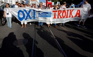 "People hold a banner reading ""Oxi Troika"" (No Troika) as they take part in a demonstration in support of Greece, in Lisbon on July 4, 2015 a day before nearly 10 million Greek voters take to the ballot booths to vote 'Yes' or 'No' in a referendum asking if they accept more austerity measures in return for bailout funds. The referendum on a deal with European governments, the European Union (EU) and International Monetary Fund (IMF), was called by Prime Minister Alexis Tsipras on the night of June 26-27.   AFP PHOTO/ JOSE MANUEL RIBEIROJOSE MANUEL RIBEIRO/AFP/Getty Images"