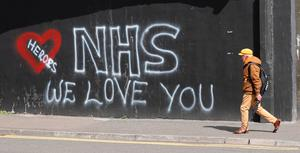 A man walks past graffiti in support of NHS staff battling the coronavirus outbreak, in the loyalist Sandy Row area of Belfast. PA Photo. Picture date: Saturday May 2, 2020. See PA story HEALTH Coronavirus Ulster. Photo credit should read: Niall Carson/PA Wire