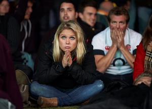Rugby fans react after watching the Pool A match of the 2015 Rugby World Cup between England and Australia at the official Fanzone at Twickenham stadium, south west London on October 3, 2015.