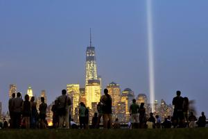 """FILE - SEPTEMBER 10, 2014: This year marks the 13th anniversary of the September 11 terrorist attacks on the United States. Various events this week will honor those who lost their lives. HOBOKEN, NJ - SEPTEMBER 11:  People attend an interfaith memorial as the """"Tribute in Light"""" shines from the Manhattan skyline next to One World Trade Center to commemorate all those who were lost on 9/11 on September 11, 2013 in Hoboken, New Jersey. The lights are located at West and Morris streets in lower Manhattan. The nation is commemorating the anniversary of the 2001 attacks which resulted in the deaths of nearly 3,000 people after two hijacked planes crashed into the World Trade Center, one into the Pentagon in Arlington, Virginia and one crash landed in Shanksville, Pennsylvania. (Photo by Michael Bocchieri/Getty Images)"""