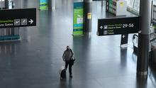 A man wearing a protective face mask walks through Terminal 2 in Dublin Airport (Brian Lawless/PA)