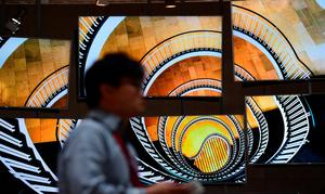 A visitor walks past a display made up of Samsung SUHD TV screens at the booth of South Korean electronics giant Samsung ahead of the opening of the 55th IFA (Internationale Funkausstellung) electronics trade fair in Berlin on September 3, 2015. AFP/Getty Images