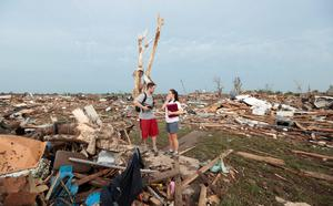 MOORE, OK- MAY 20:  Carlos and Kim Caudillo stand in the debris of their home after a powerful tornado ripped through the area on May 20, 2013 in Moore, Oklahoma. The tornado, reported to be at least EF4 strength and two miles wide, touched down in the Oklahoma City area on Monday killing at least 51 people. (Photo by Brett Deering/Getty Images)