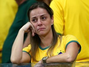 BELO HORIZONTE, BRAZIL - JULY 08: An emotional Brazil fan reacts while holding a Neymar mask after being defeated by Germany 7-1 during the 2014 FIFA World Cup Brazil Semi Final match between Brazil and Germany at Estadio Mineirao on July 8, 2014 in Belo Horizonte, Brazil.  (Photo by Robert Cianflone/Getty Images)