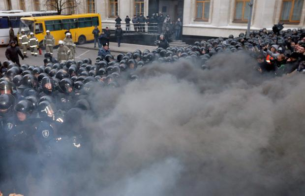 Smoke engulfs protesters and police as they clash outside the presidential office in Kiev, Ukraine, on Sunday, Dec. 1, 2013. As many as 100,000 demonstrators chased away police to rally in the center of Ukraine's capital on Sunday, defying a government ban on protests on Independence Square, in the biggest show of anger over the president's refusal to sign an agreement with the European Union. (AP Photo/Efrem Lukatsky)