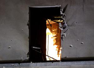 Bullet holes around a window on the back side of the house after an intervention of security forces against a group of extremists in Saint-Denis, near Paris, Wednesday, Nov. 18, 2015. (AP Photo/Michel Euler)