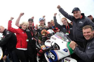 Michael Rutter celebrates his race win with team boss Ryan Farquhar and the team in the Supertwin race at the Vauxhall International North West 200. Photo Stephen Davison/Pacemaker Press