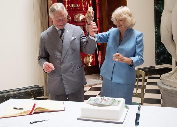 ANTRIM, NORTHERN IRELAND - MAY 22:  Prince Charles, Prince of Wales and Camilla, Duchess of Cornwall cut a cake with the help of Mr David Lindsay, HM Lord-Lieutenant of County Down during their visit to Mount Stewart House and Garden on May 22, 2015 in Newtownards, Northern Ireland. Prince Charles, Prince of Wales and Camilla, Duchess of Cornwall visited Mount Stewart House and Gardens and Northern Ireland's oldest peace and reconciliation centre Corrymeela on the final day of their visit of Ireland.  (Photo by Eddie Mulholland - Pool/Getty Images)