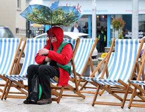 Golf Volunteer Ken McCaw from Holywood sheltering under an upturned umbrella  during a heavy rain shower surrounded by empty deckchairs on the Newcastle Promanade, while the second day of the Dubai Duty Free Irish Open was played at Royal County Down. Northern Ireland- 29th  May   2015