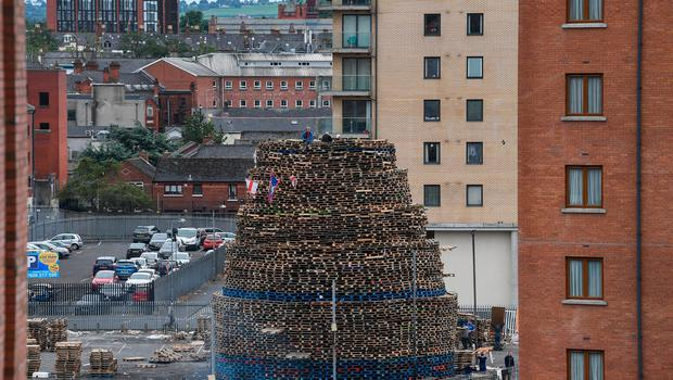 BELFAST, NORTHERN IRELAND - JULY 10:  Loyalists sit on the Sandy Row bonfire being built in preparation for the 11th night bonfire on July 10, 2017 in Belfast.  (Photo by Jeff J Mitchell/Getty Images)
