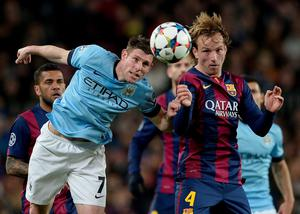 Barcelona's Croatian midfielder Ivan Rakitic (R) vies with Manchester City's midfielder James Milner during the UEFA Champions League round of 16 football match FC Barcelona vs Manchester City at the Camp Nou stadium in Barcelona on March 18, 2015. AFP PHOTO/ JOSEP LAGOJOSEP LAGO/AFP/Getty Images