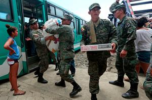 Soldiers distributed supplies in Jama, in the Ecuadorean coastal province of Manabi, on April 18, 2016 two days after a 7.8-magnitude quake hit the country, on April 18, 2016. Rescuers and desperate families clawed through the rubble Monday to pull out survivors of an earthquake that killed 350 people and destroyed towns in a tourist area of Ecuador. / AFP PHOTO / Juan CevallosJUAN CEVALLOS/AFP/Getty Images