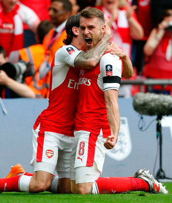 Cup kings: Arsenal's match winner Aaron Ramsey celebrates his goal with Hector Bellerin