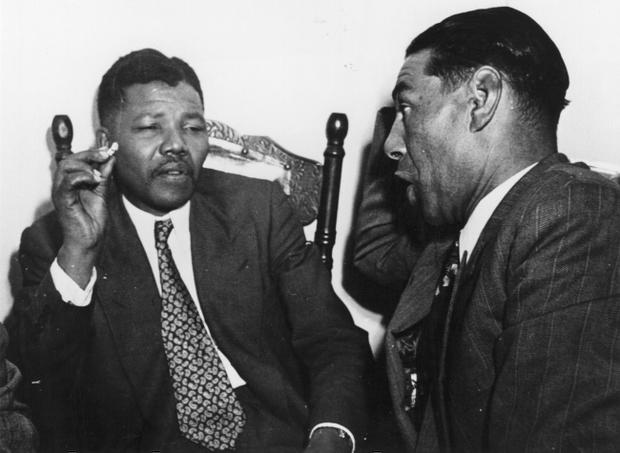 (FILE PHOTO) Former South African President Nelson Mandela Has Died Aged 95 circa 1964: Nelson Mandela, President of the African National Congress (left) in discussion with C Andrews, a Cape Town teacher.    (Photo by Three Lions/Getty Images)