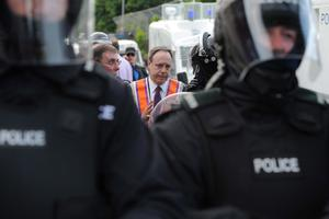 12/7/13 PACEMAKER PRESS BELFAST. MP Nigel Dodds talks to senior police officers as serious trouble broke out this evening as Police enforced the Parades Commission's ruling that Orange bandsmen could not return past the nationalist Ardoyne area after the 12th of July annual parade. Picture Charles McQuillan/Pacemaker.