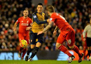 Arsenal's German midfielder Mesut Ozil (L) passes the ball during the English Premier League football match between Liverpool and Arsenal at Anfield stadium in Liverpool, north-west England on January 13, 2016. AFP PHOTO / PAUL ELLIS RESTRICTED TO EDITORIAL USE. NO USE WITH UNAUTHORIZED AUDIO, VIDEO, DATA, FIXTURE LISTS, CLUB/LEAGUE LOGOS OR 'LIVE' SERVICES. ONLINE IN-MATCH USE LIMITED TO 75 IMAGES, NO VIDEO EMULATION. NO USE IN BETTING, GAMES OR SINGLE CLUB/LEAGUE/PLAYER PUBLICATIONS.PAUL ELLIS/AFP/Getty Images