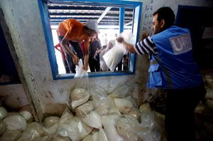 Palestinians crowd a window for food aid at a United Nations distribution centre in the Shati refugee camp in Gaza City, Wednesday, Aug. 6, 2014. (AP Photo/Hatem Moussa)