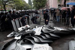 Ukrainian police officers remove shields which their comrades from another unit set down earlier outside the police headquarter in Odessa, Ukraine, Sunday, May 4, 2014.  (AP Photo/Sergei Poliakov)