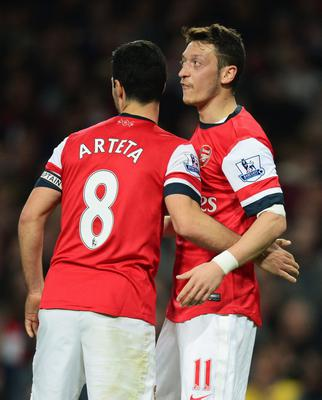 LONDON, ENGLAND - APRIL 28:  Mesut Oezil of Arsenal (11) celebrates with Mikel Arteta as he scores their second goal during the Barclays Premier League match between Arsenal and Newcastle United at Emirates Stadium on April 28, 2014 in London, England.  (Photo by Jamie McDonald/Getty Images)