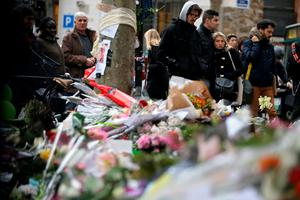 People spend a moment mourning the dead at the site of the attack at the Cafe Belle Equipe on rue de Charonne, prior to going to work early on November 16, 2015 in Paris, three days after the terrorist attacks that left over 130 dead and more than 350 injured. France prepared to fall silent at noon on November 16 to mourn victims of the Paris attacks after its warplanes pounded the Syrian stronghold of Islamic State, the jihadist group that has claimed responsibility for the slaughter. AFP PHOTO / KENZO TRIBOUILLARDKENZO TRIBOUILLARD/AFP/Getty Images