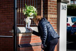 A passer by stops at the gates of Connolly House, Andersonstown, Belfast to read a message from Gerry Adams after the death of Northern Ireland's former deputy first minister and ex-IRA commander Martin McGuinness aged 66. Liam McBurney/PA Wire
