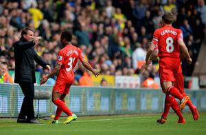 NORWICH, ENGLAND - APRIL 20:  Raheem Sterling of Liverpool celebrates scoring the opening goal with Manager Brendan Rodgers of Liverpool during the Barclays Premier League match between Norwich City and Liverpool at Carrow Road on April 20, 2014 in Norwich, England.  (Photo by Michael Regan/Getty Images)