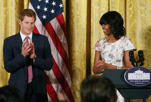 WASHINGTON, DC - MAY 09:  HRH Prince Harry (L), stands with first lady Michelle Obama (R) during an event to honor military families at the White House on May 9, 2013 in Washington, DC. HRH will be undertaking engagements on behalf of charities with which the Prince is closely associated on behalf also of HM Government, with a central theme of supporting injured service personnel from the UK and US forces.  (Photo by Mark Wilson/Getty Images)