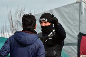 "A policeman gestures with a man as agents dismantle shelters on February 29, 2016 in the ""jungle"" migrants and refugees camp in Calais, northern France.  A French court on February 25 gave the green light to plans to evacuate hundreds of migrants from the southern half of the sprawling camp in the port town, with many wanting to stay near the entrance to the Channel Tunnel, the gateway to their ultimate goal of Britain. AFP PHOTO / PHILIPPE HUGUENPHILIPPE HUGUEN/AFP/Getty Images"