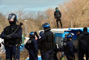 "A man refusing to leave stands on a shelter's roof next to anti-riot policemen as agents dismantle shelters on February 29, 2016 in the ""jungle"" migrants and refugees camp in Calais, northern France.  A French court on February 25 gave the green light to plans to evacuate hundreds of migrants from the southern half of the sprawling camp in the port town, with many wanting to stay near the entrance to the Channel Tunnel, the gateway to their ultimate goal of Britain. AFP PHOTO / PHILIPPE HUGUENPHILIPPE HUGUEN/AFP/Getty Images"