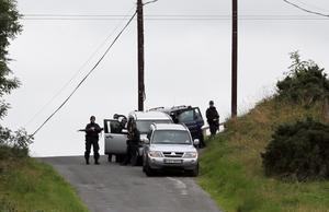Police at the scene near the village of Cullyhanna, Northern Ireland, where a dissident republican-style rocket launcher has been discovered.  PRESS ASSOCIATION Photo. Picture date: Wednesday August 28, 2013. Troops were involved in a massive security operation close to the border with the Irish Republic in south Armagh. The alert, near the village of Cullyhanna, has been continuing for several days. See PA story ULSTER Alert. Photo credit should read: Paul Faith/PA Wire
