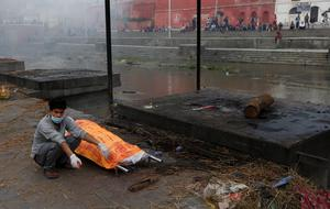 A Nepalese man waits for the cremation of his relative killed in the recent earthquake, at the Pashupatinath temple, on the banks of Bagmati river, in Kathmandu, Nepal, Monday, April 27, 2015. A strong magnitude earthquake shook Nepals capital and the densely populated Kathmandu valley on Saturday devastating the region and leaving some tens of thousands shell-shocked and sleeping in streets.  (AP Photo / Manish Swarup)