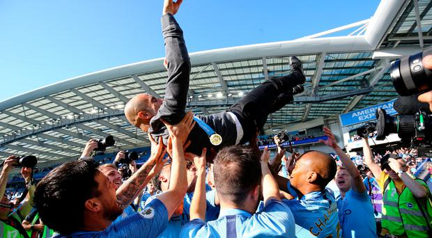 Celebrations: Pep Guardiola is lifted aloft by Manchester City players after they sealed the title at Brighton last week
