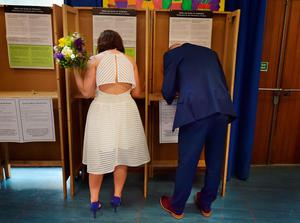 Newly married couple Anne Fox (nee Cole) and Vincent Fox celebrate their wedding day by showing their support for the Yes campaign in favour of same-sex marriage as they cast their votes at a polling station on May 22, 2015 in Dublin, Ireland. (Photo by Charles McQuillan/Getty Images)