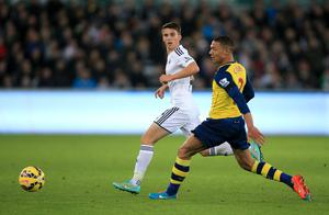 Swansea City's Tom Carroll (left) and Arsenal's Kieran Gibbs battle for the ball during the Barclays Premier League match at the Liberty Stadium, Swansea. Nick Potts/PA Wire.