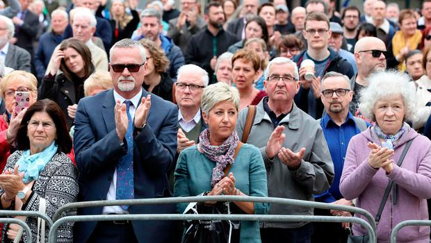 Mourners gesture as pallbearers carry the coffin of journalist Lyra McKee (29), who was killed by a dissident republican paramilitary in Northern Ireland on April 18, during the funeral service at St Anne's Cathedral in Belfast on April 24, 2019.