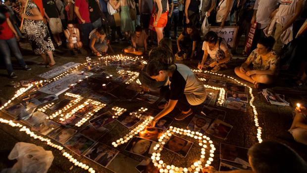 """Israeli left wing activists light candles with shape of the word """"Sorry"""" in Hebrew and place portraits on the ground of Israelis and Palestinians who have been killed in the conflict, during a demonstration against the Gaza war, in Tel Aviv, Israel, Saturday, July 26, 2014. (AP Photo/Dan Balilty)"""