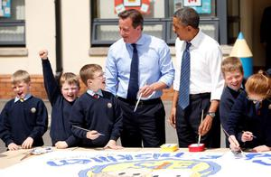 President Barack Obama and Prime Minister David Cameron help out as students work on a school project about the G8 summit during a visit to the Enniskillen Integrated Primary School in Enniskillen, Northern Ireland ahead of the G8 summit. PRESS ASSOCIATION Photo. Picture date: Monday June 17, 2013. See PA story POLITICS G8. Photo credit should read: Matt Dunham/PA Wire