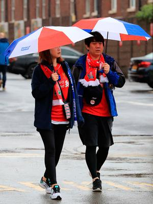 """Fans arrive in the wet weather before the Premier League match at Anfield, Liverpool. PRESS ASSOCIATION Photo. Picture date: Saturday April 1, 2017. See PA story SOCCER Liverpool. Photo credit should read: Peter Byrne/PA Wire. RESTRICTIONS: EDITORIAL USE ONLY No use with unauthorised audio, video, data, fixture lists, club/league logos or """"live"""" services. Online in-match use limited to 75 images, no video emulation. No use in betting, games or single club/league/player publications."""