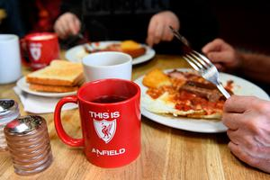 LIVERPOOL, ENGLAND - APRIL 01: Liverpool fans enjoy some pre match food with a Liverpool mug in a local cafe prior to the Premier League match between Liverpool and Everton at Anfield on April 1, 2017 in Liverpool, England.  (Photo by Gareth Copley/Getty Images)