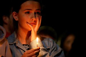 A woman holds a candle during a candlelight vigil at the Martin Luther King Jr. Civic Center Park to mourn the loss of six students who died in an early Tuesday morning balcony collapse on June 17, 2015 in Berkeley, California. Hundreds of people attended a candlelight vigil for six students who were killed, five of which were in the United States on J1 work visas from Ireland, when a balcony they were standing on collapsed during a birthday party in their Berkeley, California apartment.  (Photo by Justin Sullivan/Getty Images)