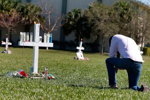 A mourner kneels in front of a memorial for the victims of the Marjory Stoneman Douglas High School shooting in a park in Parkland, Florida on February 16, 2018.  A former student, Nikolas Cruz, opened fire at the Florida high school leaving 17 people dead and 15 injured. / AFP PHOTO / RHONA WISERHONA WISE/AFP/Getty Images