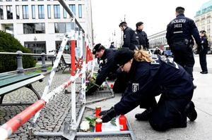 German police officers arrange flowers brought by people behind a fence set up by the police outside French Embassy in Berlin on November 14, 2015, a day after deadly attacks in Paris. The string of coordinated attacks in and around Paris late November 13, 2015 left more than 120 people dead, in the worst such violence in France's history.  AFP PHOTO / TOBIAS SCHWARZTOBIAS SCHWARZ/AFP/Getty Images
