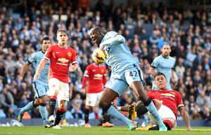 Manchester City's Yaya Toure is tackled by Manchester United's Marcos Rojo (right) during the Barclays Premier League match at the Etihad Stadium, Manchester. Martin Rickett/PA Wire.
