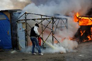 A migrant uses a fire extinguisher on a group of burning tents in a makeshift camp near Calais, France,  Monday Feb. 29, 2016. Under the eye of hundreds of riot police, workers began pulling down tents and makeshift shelters in the sprawling camp in Calais on Monday, dismantling the fragile structures that have served as temporary homes for migrants hoping to make their way to a better life in Britain. (AP Photo/Jerome Delay)