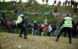 Migrants attempt to overrun a police cordon by the perimeter fence of the Eurotunnel site at Coquelles in Calais, France. PRESS ASSOCIATION Photo. Picture date: Thursday July 30, 2015. Nine people have been killed attempting to cross the Channel in the last month, according to Eurotunnel, as migrants try to reach Britain. See PA story POLITICS Calais. Photo credit should read: Yui Mok/PA Wire