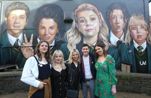 Derry Girls cast members Louisa Harland, Nicola Coughlan, Saoirse-Monica Jackson, Dylan Llewellyn, and creator Lisa McGee at the 'Derry Girls' mural painted by UV Artists on the gable wall of Badger's Bar. Credit: Lorcan Doherty/Press Eye