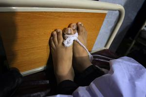 The feet of a victim of a Taliban attack in a school are tied together  at a local hospital in Peshawar, Pakistan,Tuesday, Dec. 16, 2014. Taliban gunmen stormed a military-run school in the northwestern Pakistani city of Peshawar on Tuesday, killing and wounding scores, officials said, in the highest-profile militant attack to hit the troubled region in months.(AP Photo/Mohammad Sajjad)